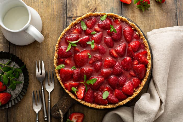 Overhead view of assembled fresh strawberry pie on a wooden table, surrounded by forks and napkins