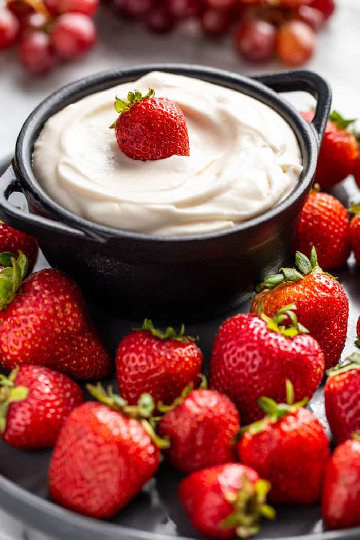 Close up of fruit dip in a serving bowl surrounded by whole strawberries