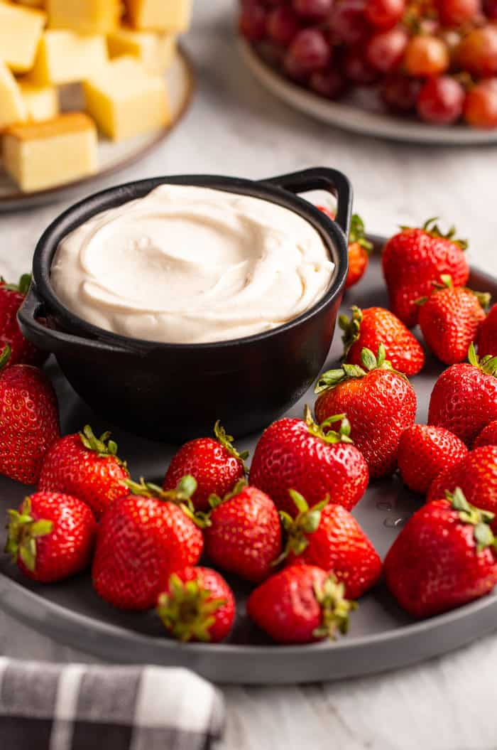 Fruit dip on a serving platter surrounded by strawberries, set on a marble countertop