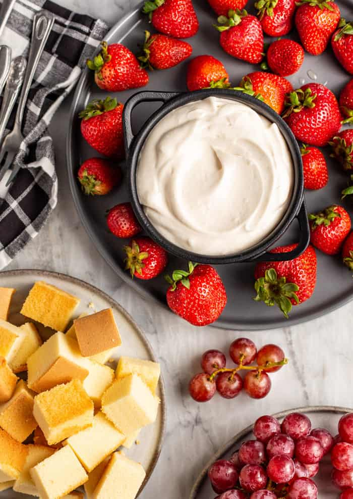 Plates of strawberries, cubed pound cake, and grapes on a marble countertop with a bowl of fruit dip
