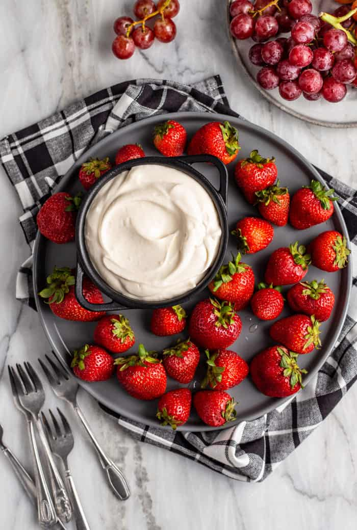 Black plate holding whole strawberries and a bowl of fruit dip set on a blue plaid dish towel