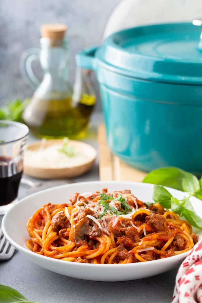 White serving bowl filled with one-pot spaghetti, with the dutch oven and a glass of wine in the background