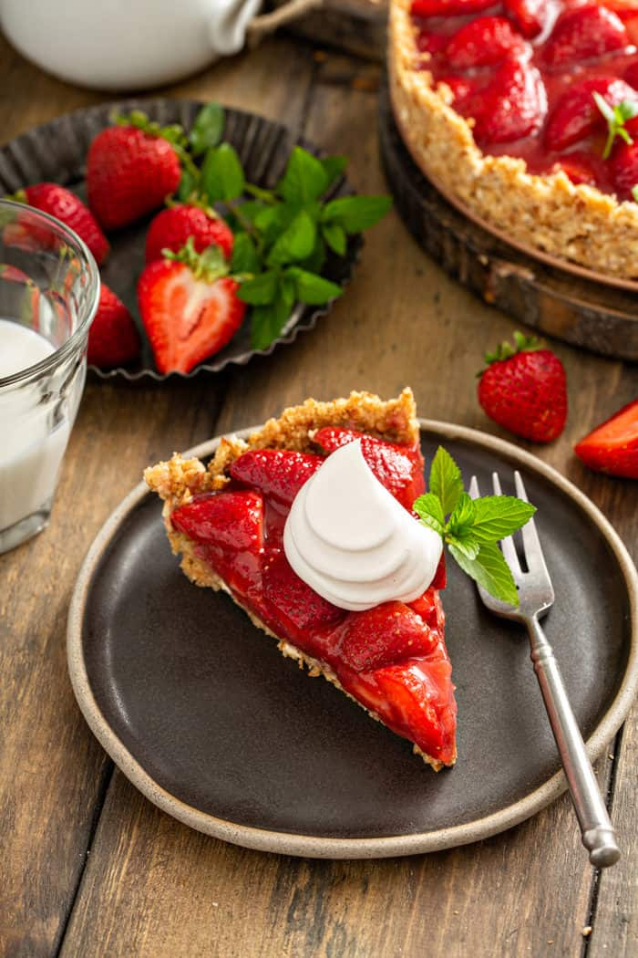 Slice of fresh strawberry pie, topped with a dollop of whipped cream, on a black plate