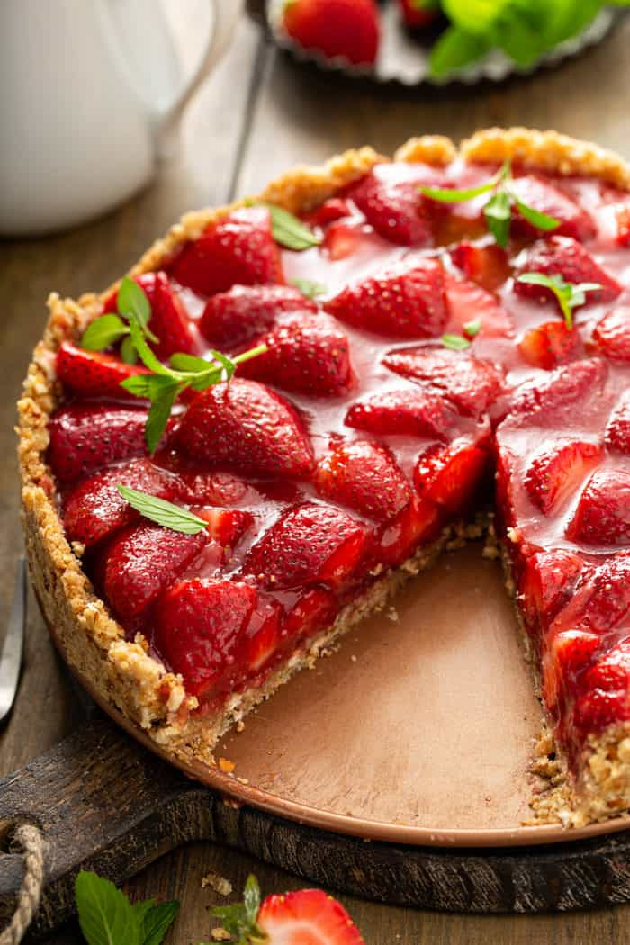 Fresh strawberry pie with a slice cut out of it