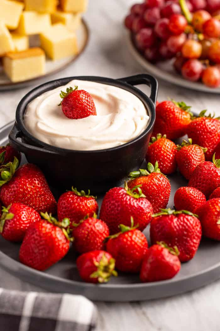 Strawberries surrounding a bowl of fruit dip on a black plate. A whole strawberry sits on top of the dip.