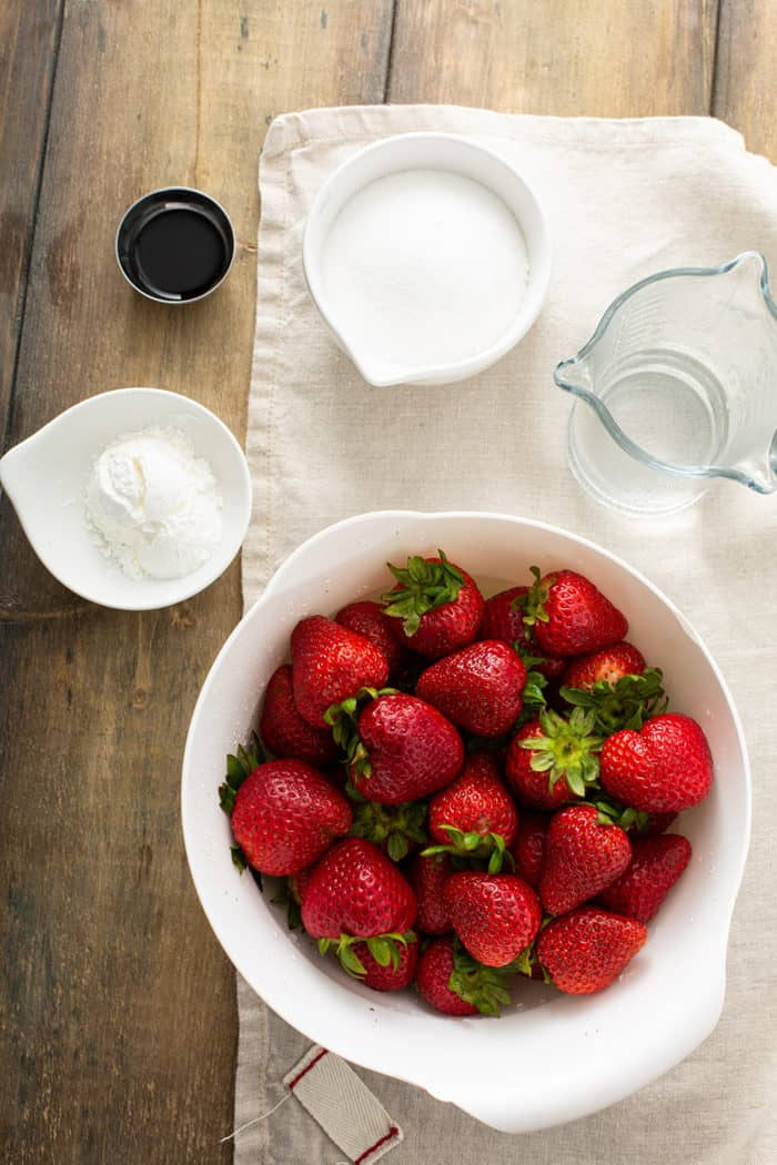 Ingredients for fresh strawberry pie filling arranged on a wooden table