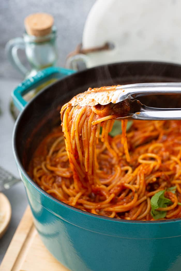 Tongs pulling a serving of one-pot spaghetti out of the pot