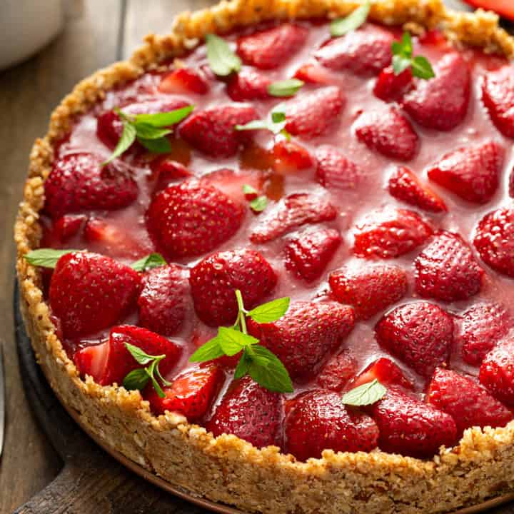 Close up of an assembled and set fresh strawberry pie garnished with mint leaves