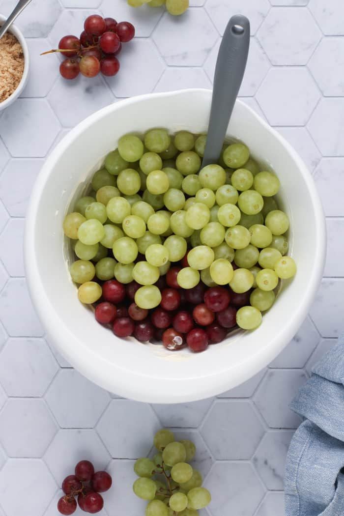 Spatula about to fold red and green grapes into a dressing for creamy grape salad
