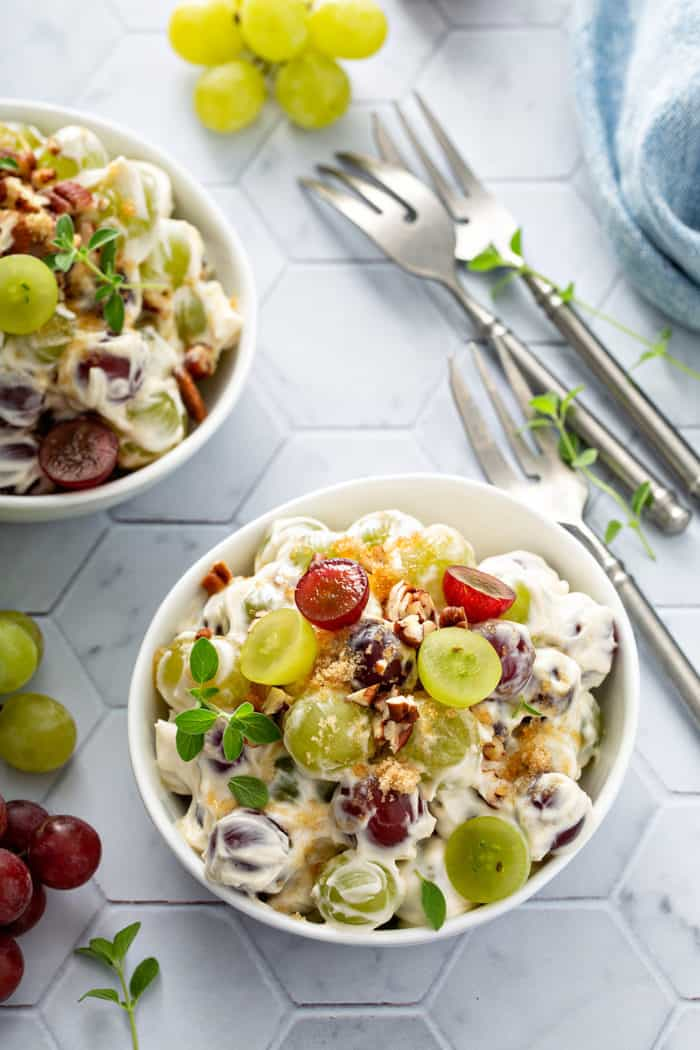 Two small bowls filled with creamy grape salad next to forks on a tiled countertop