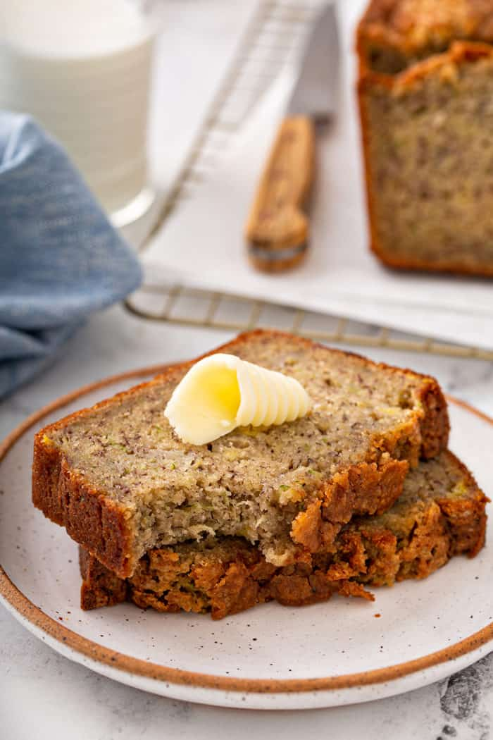 Buttered slice of zucchini banana bread with a bite taken out of it on a plate