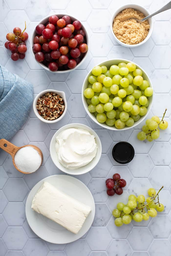 Ingredients for creamy grape salad arranged on a tile countertop
