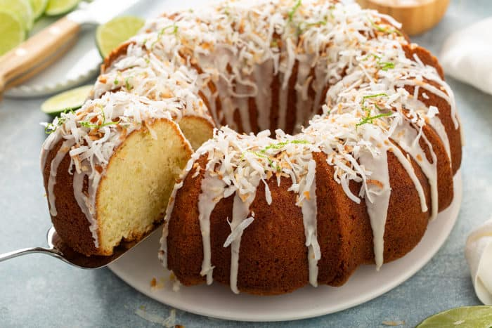 Cake server pulling a slice of lime coconut cake out of the cake