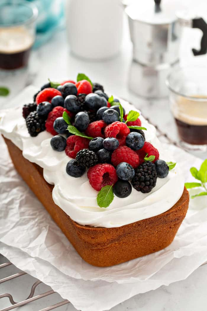 Loaf of lemon whipping cream cake topped with whipped cream and fresh berries