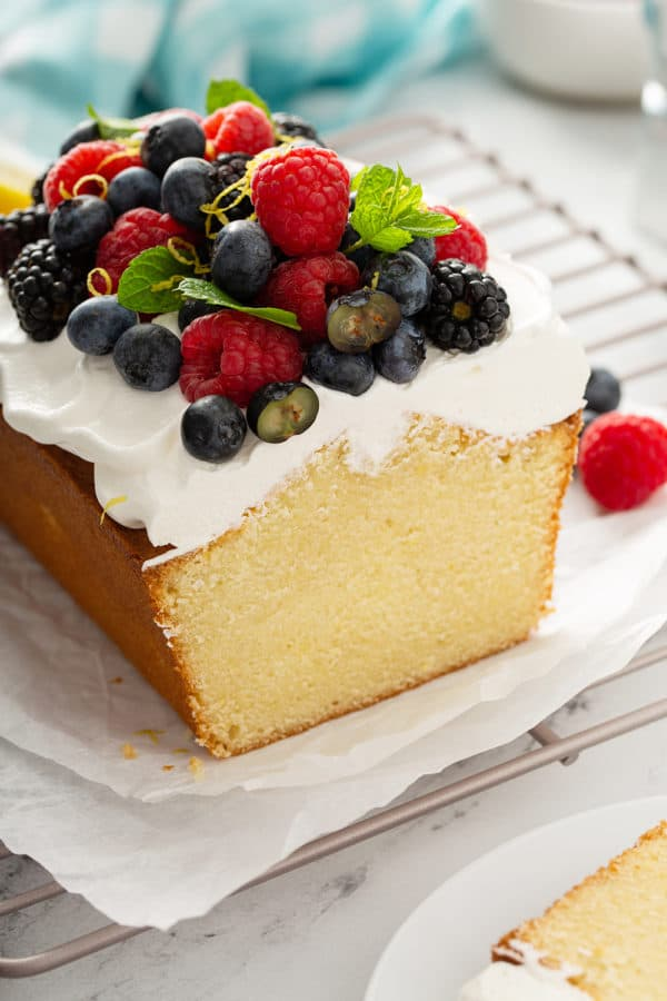 Cross view of sliced lemon whipping cream cake, topped with whipped cream and berries