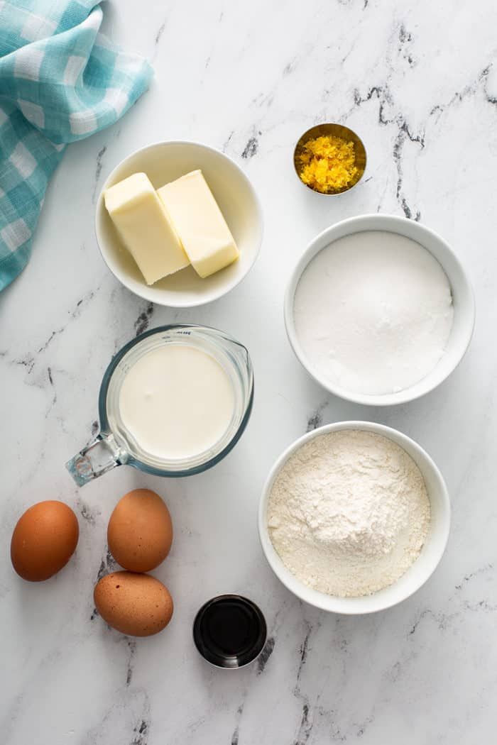 Overhead view of ingredients for lemon whipping cream cake arranged on a marble countertop