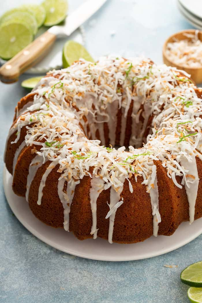 Glazed lime coconut cake on a white cake plate, garnished with lime zest and toasted coconut