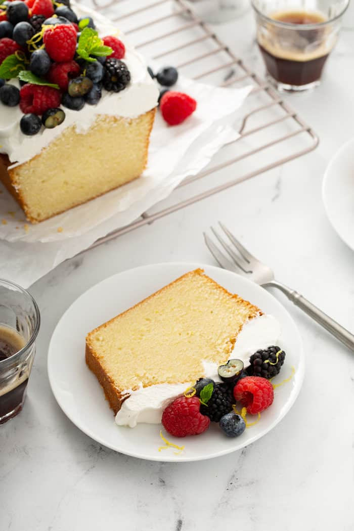 Slice of lemon whipping cream cake on a white plate, with a fork and more cake on the counter next to it