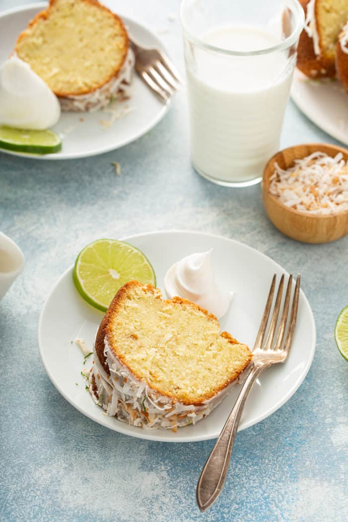 Two white plates with slices of lime coconut cake next to a glass of milk