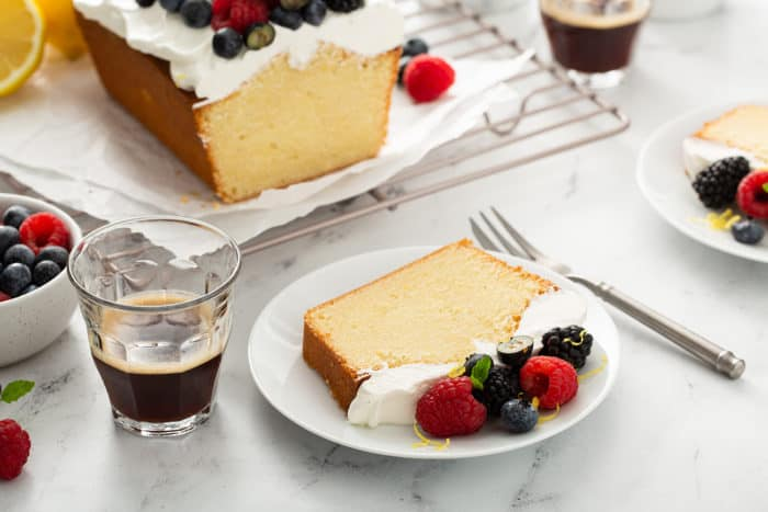 Plates of lemon whipping cream cake next to cups of espresso on a marble counter