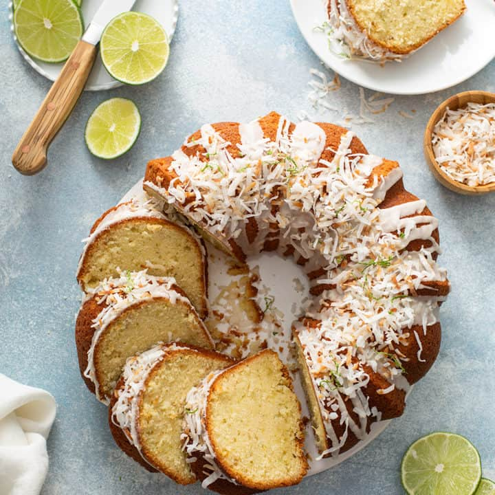 Sliced lime coconut cake surrounded by sliced limes