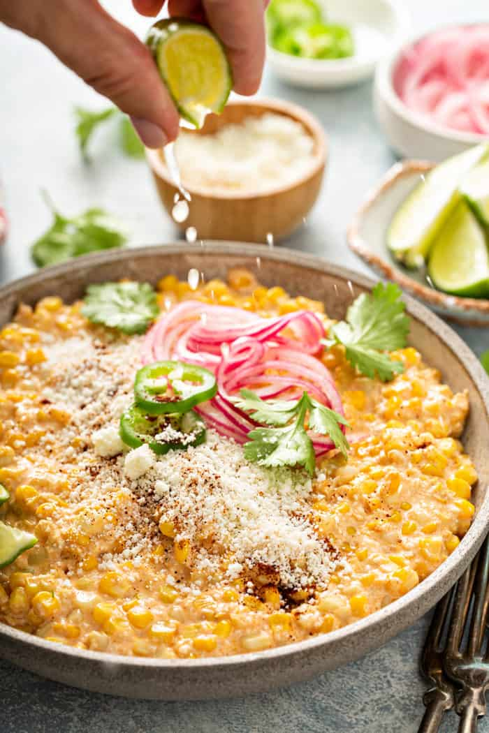 Hand squeezing a wedge of lime over the top of a bowl of Mexican street corn salad