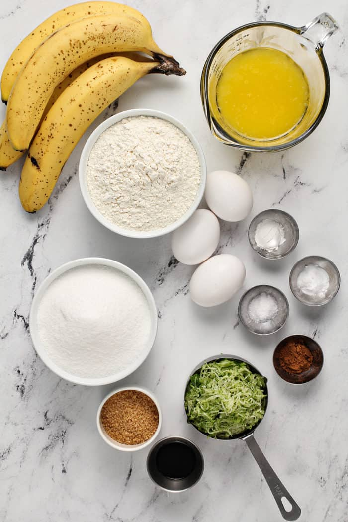 Ingredients for zucchini banana bread arranged on a marble countertop