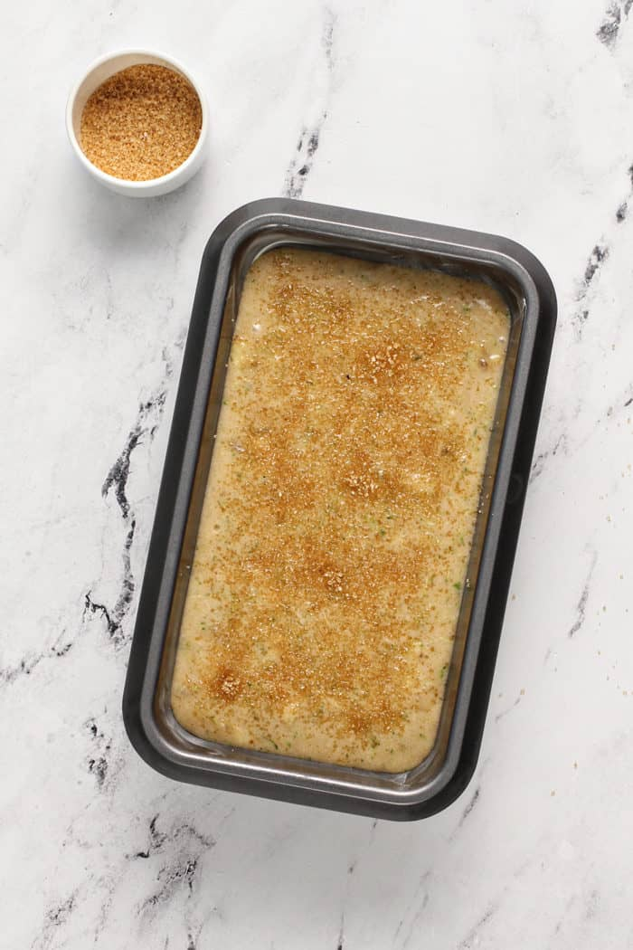 Zucchini banana bread batter in a loaf pan, sprinkled with turbinado sugar, ready to bake