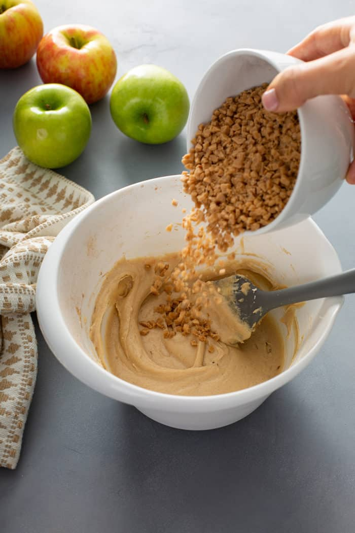 Toffee bits being added to a bowl of apple dip
