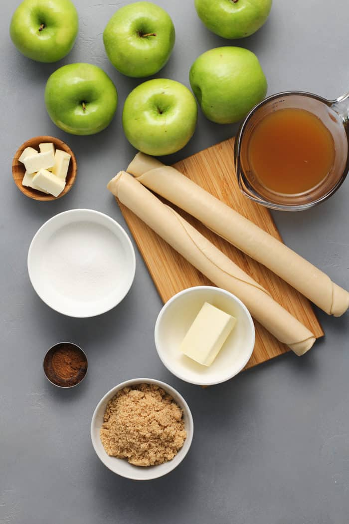Ingredients for old-fashioned apple dumplings arranged on a gray countertop