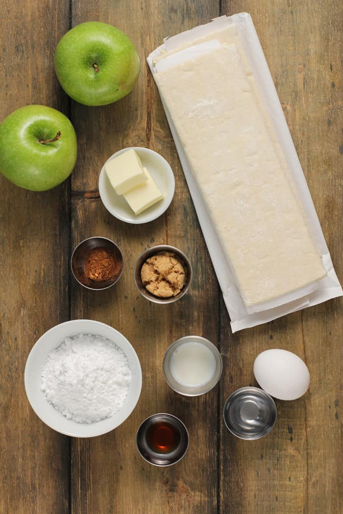 Apple turnover ingredients arranged on a wooden countertop