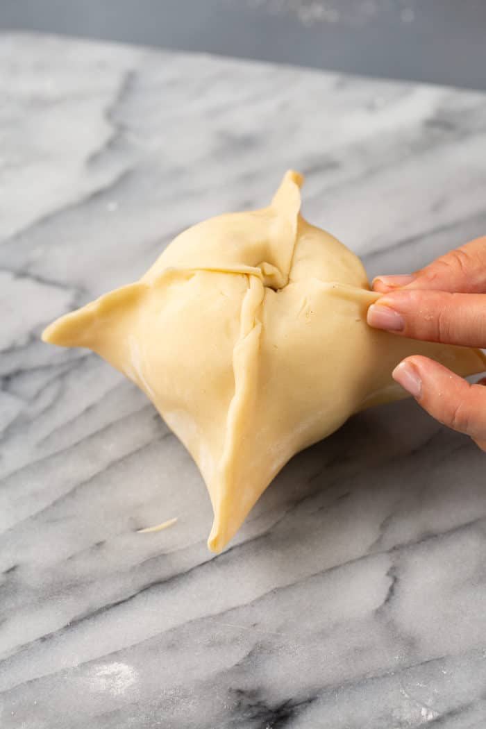 Pie dough wrapped around an apple, set on a marble countertop
