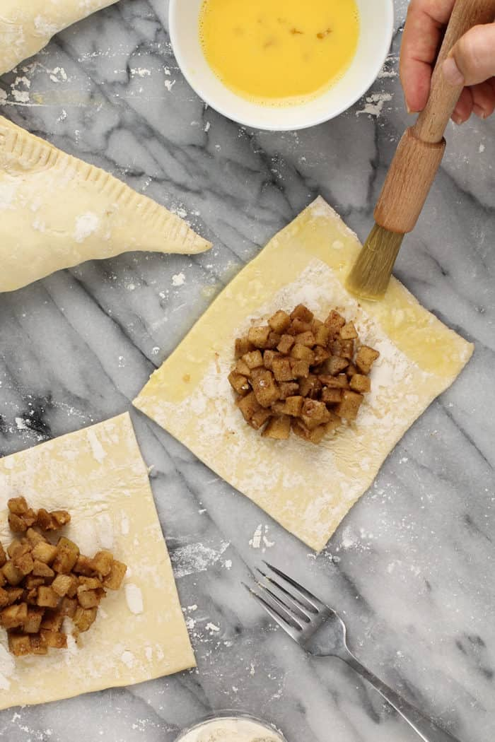 Egg wash being brushed on the edges of apple turnover dough, ready to fold in half