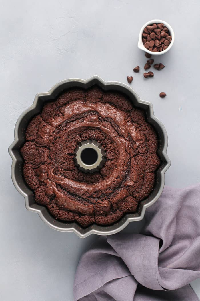 Baked chocolate bundt cake cooling in the pan on a gray counter