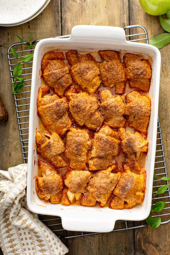 Baked easy apple dumplings in a white baking dish, set on a wire cooling rack
