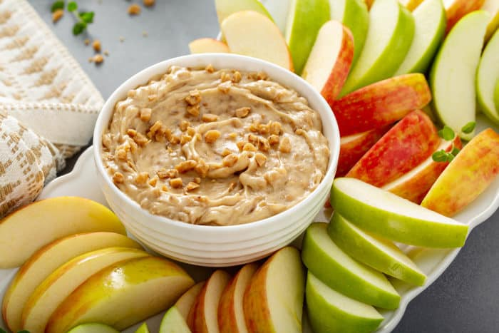 Bowl of toffee apple dip surrounded by slices of fresh red and green apples