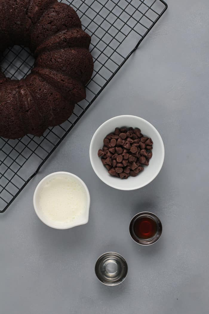 Ingredients for chocolate ganache next to a wire rack holding a chocolate bundt cake