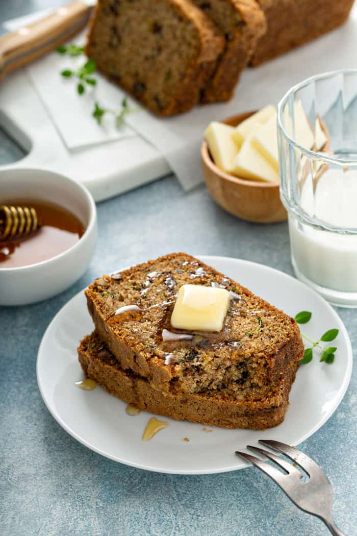 Two slices of classic zucchini bread on a plate, topped with butter and honey