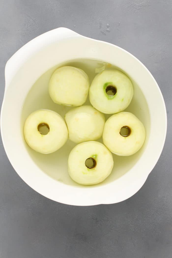 Peeled and cored apples set in a white bowl filled with water