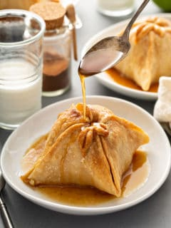 Spoon pouring sugar syrup over the top of a plated old-fashioned apple dumpling