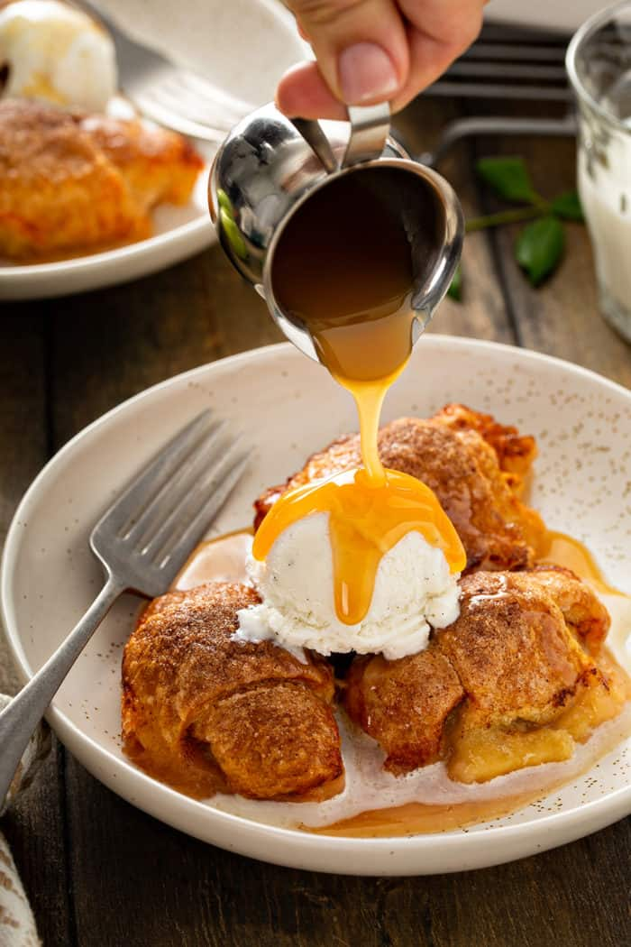 Caramel sauce being poured over easy apple dumplings and a scoop of vanilla ice cream in a cream bowl