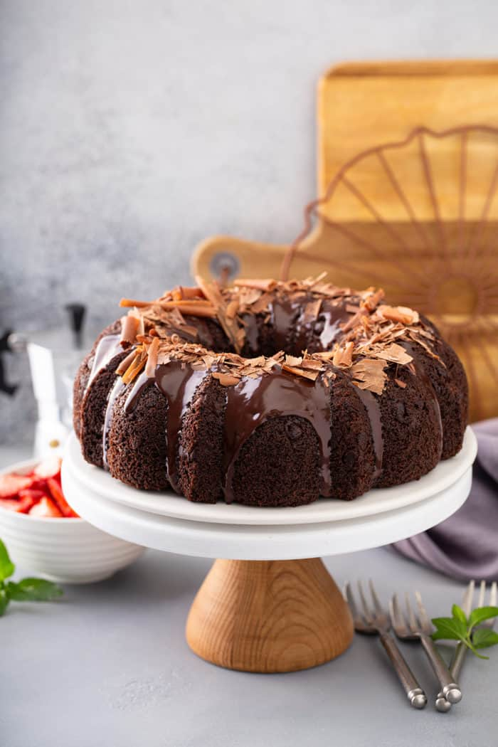 Chocolate bundt cake topped with ganache and chocolate shavings on a cake plate with berries and espresso in the background