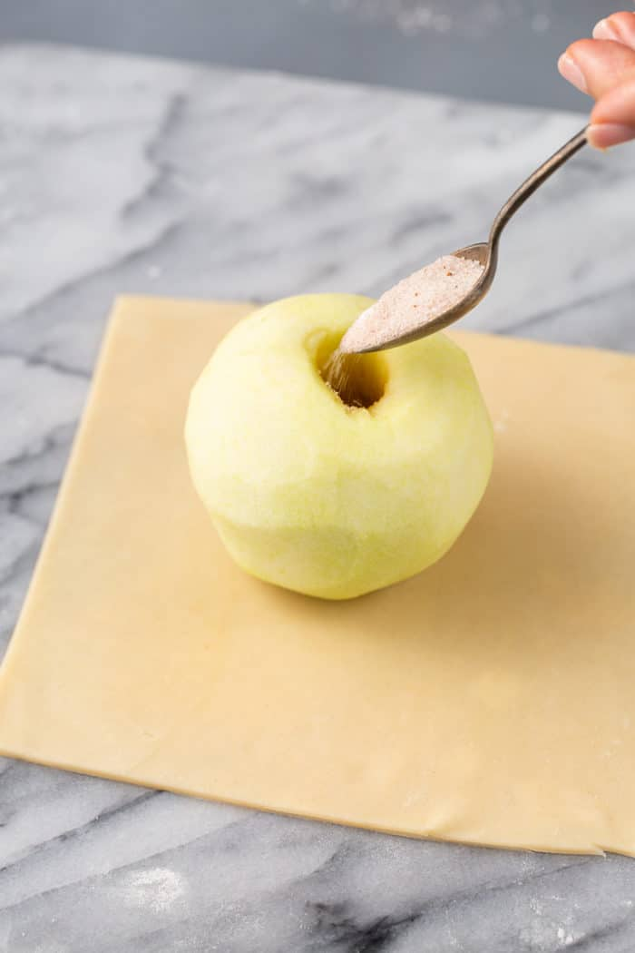 Spoon pouring spiced sugar into the center of a peeled and cored apple that is set in the center of a square of pie dough