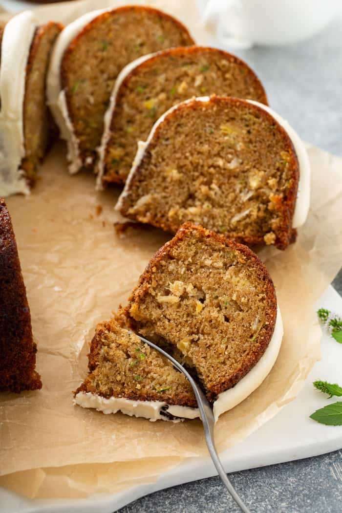 Fork cutting into a slice of zucchini bundt cake set on a piece of parchment paper, with more slices of cake in the background