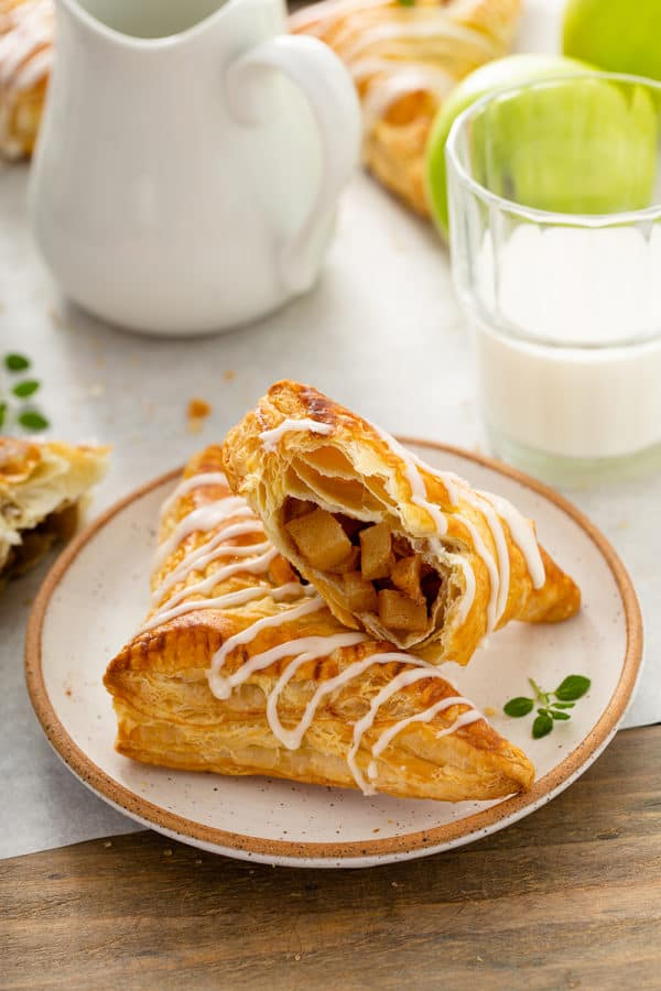 Two apple turnovers arranged on a plate, with one of the turnovers cut in half to show the filling inside