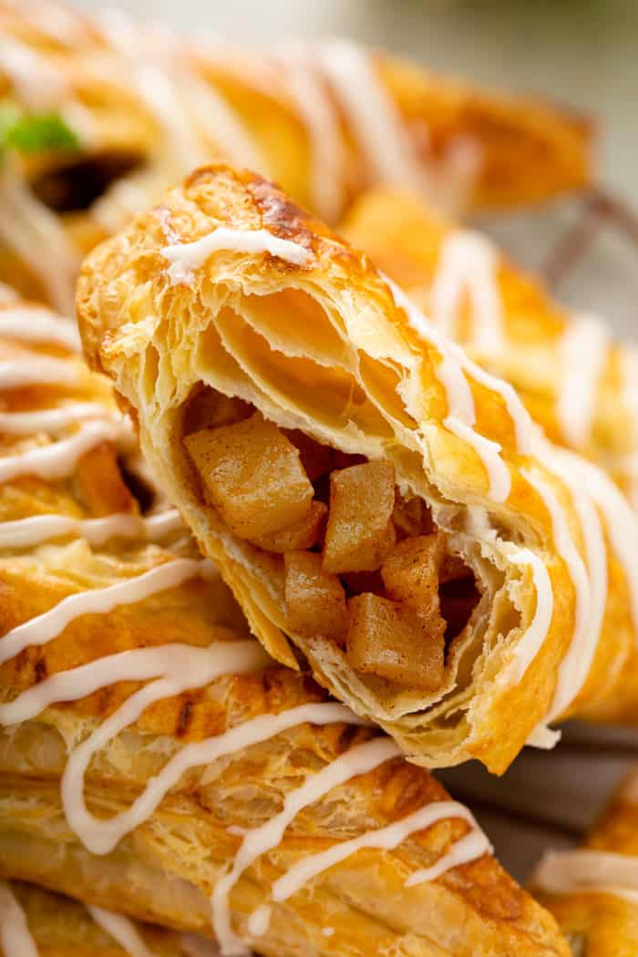 Close up of an apple turnover that has been cut in half to show the filling inside