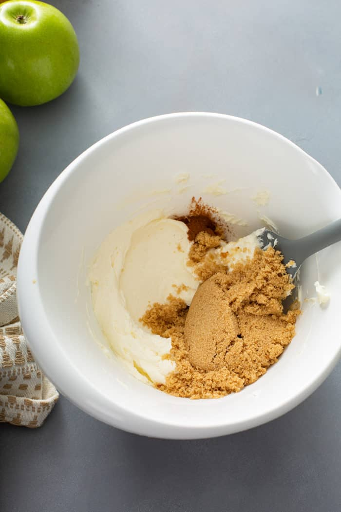 Brown sugar and vanilla being added to whipped cream cheese to make apple dip