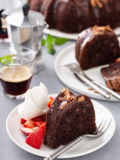 Plates of easy chocolate bundt cake next to a cake plate and cups of espresso