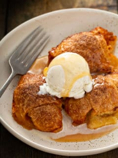 Easy apple dumplings topped with a scoop of ice cream and caramel sauce nestled in a cream bowl