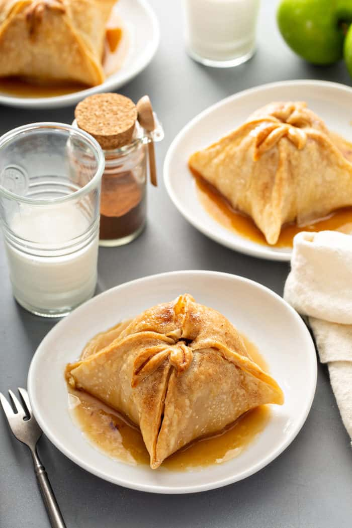 Three white plates containing old-fashioned apple dumplings set on a gray countertop